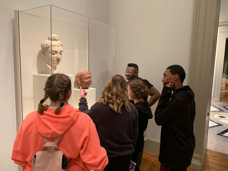 Five Youth Art Team artists standing together while looking at the heads from two ancient Middle Eastern sculptures.
